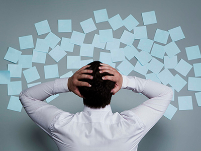 A man photographed from behind with his hands on his head as he looks at a wall full of sticky-notes.