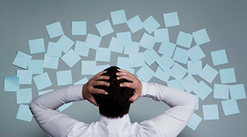 A businessman or manageer photographed from behind with his hands on his head while looking at a mess of sticky notes on the wall.