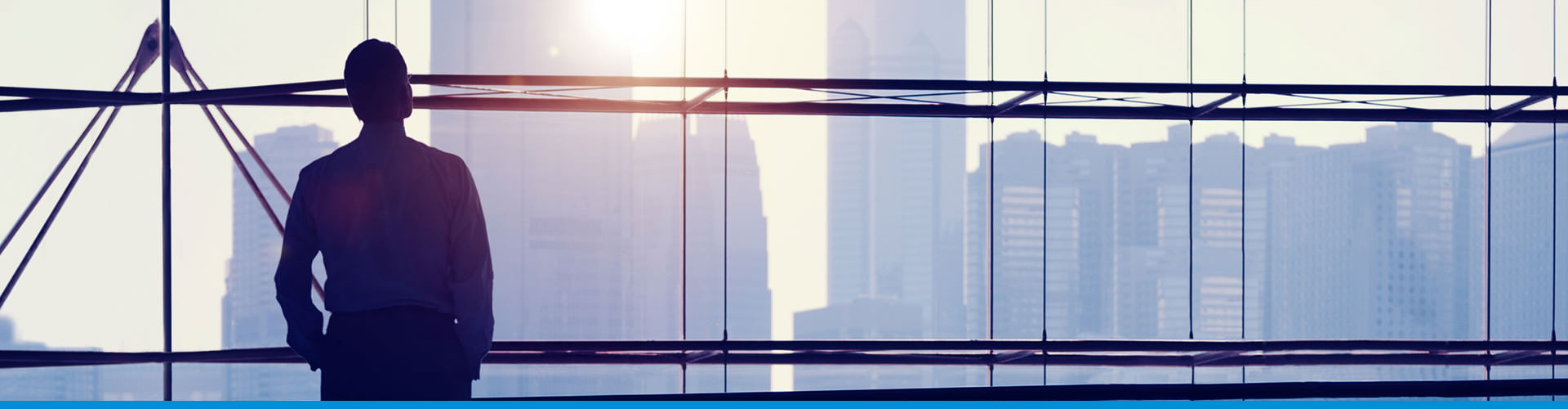 A business executive looks out the window of a boardroom as the sun sets or rises behind an urban skyline.